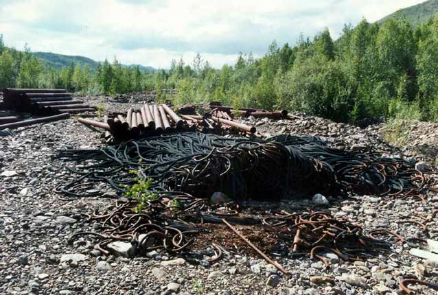 large pile of metal tubes and cables or hoses on rocky ground, surrounded by forests