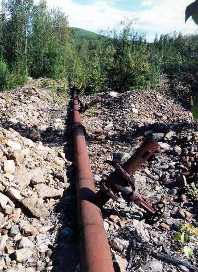 long rusty pipe running along a rocky surface in a forest