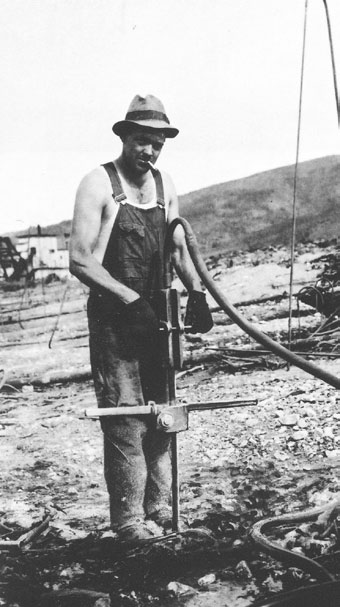 man in overalls standing next to a device stuck in the ground