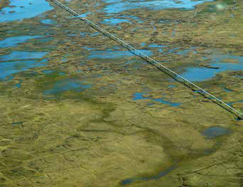 aerial view of a pipeline traveling across a landscape of bogs and lakes