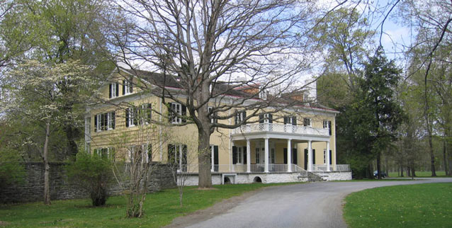 A driveway curves in front of a large Federal style mansion, symmetrical with flat facades.