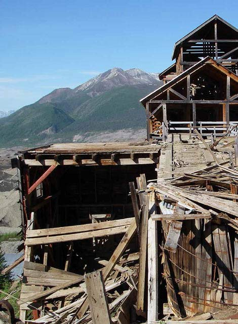 multi-story dilapidated wood building in a mountain setting