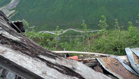 Looking downhill from the top of a sheet metal roof at a creek or narrow road