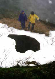two people standing over a mine opening in the ground