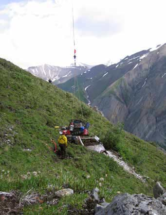 man standing next to a pile of equipment dangling on a rope, on a grassy mountainside