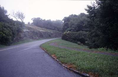 A road, framed by a rock retaining wall, winds through a hilly and partially-forested landscape.