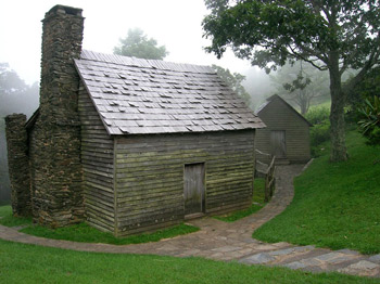The Brinegar Cabin has two stone chimneys, wooden siding, and a shingled roof.
