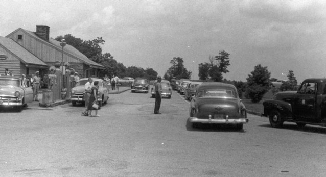 People and cars gather along the paved parking area in front of the service station building.