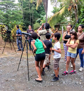 A group of children in Costa Rica line up to look through a bird spotting scope.