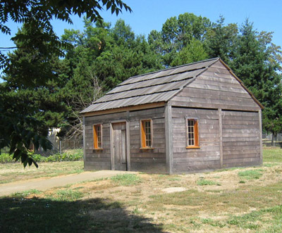 A small log house has a wood-shingled roof, several windows, and a door.