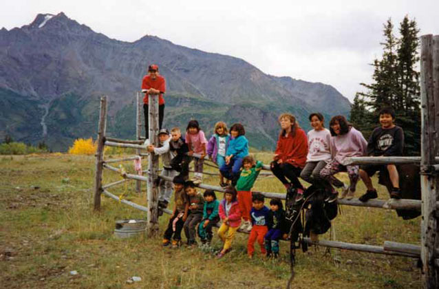 sixteen kids of various ages posing for a photo on a split rail fence in a mountainous landscape