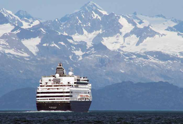 a huge cruise ship on the ocean with snowy mountains in the distance