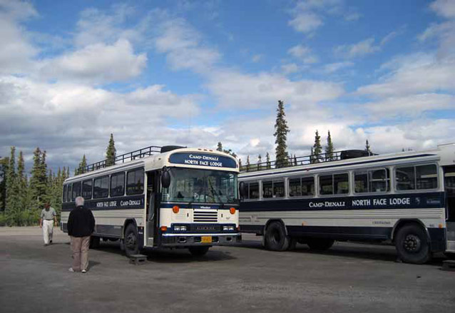 two buses in a gravel parking lot