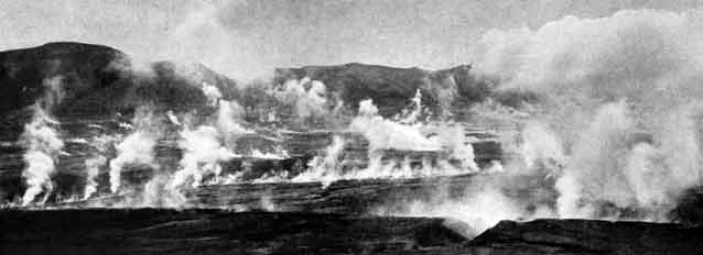 black and white image of smoke rising from a rocky landscape