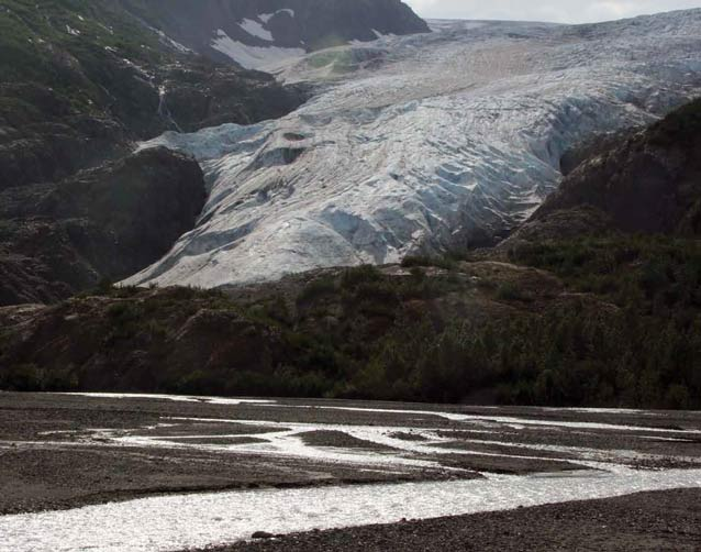 a huge glacier leading to a narrow, braided river