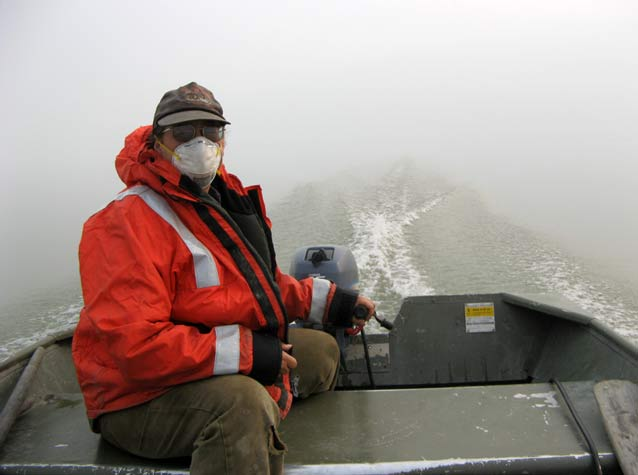 woman in a surgical mask on a boat, surrounded by thick smoke