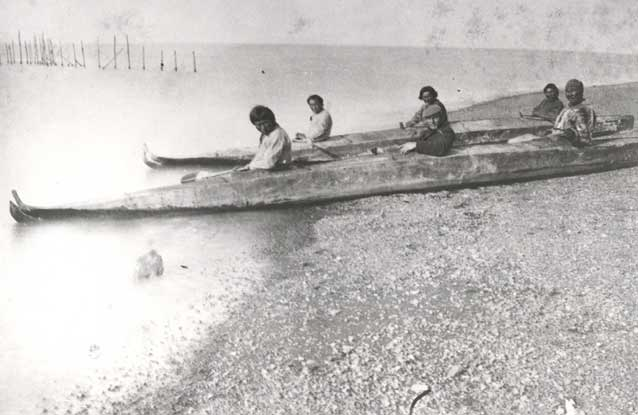 six people sitting in two long kayaks on a gravelly beach