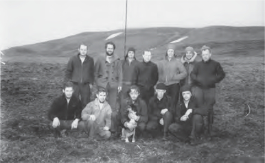 A group of men and a dog pose in two rows for photo.