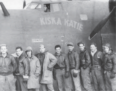 A group of men stand pose for photo in front of an airplane.
