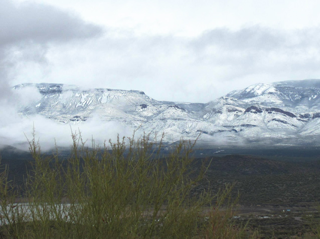 Snow blanketing highlands, viewed from an area free of snow.