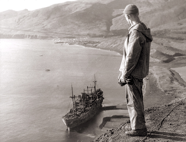 A soldiers stands on island high above a ship and gazes down on it.