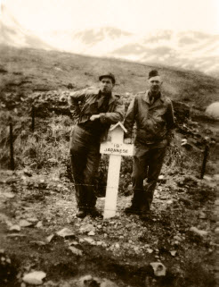 Two soldiers pose near a Japanese grave marker.