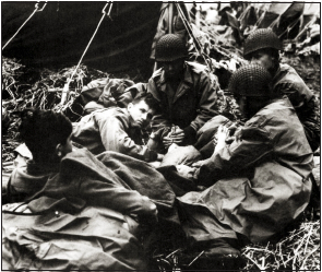 Four soldiers gather around a fifth soldier and rub his feet.