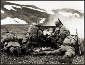 Four soldiers laying huddled behind a gun while firing.