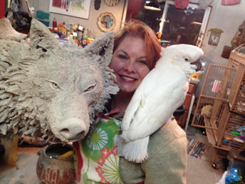 Woman in artist studio with bird and wolf sculpture