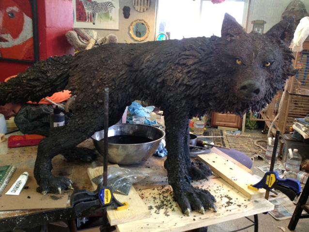 Finished wolf sculpture on work bench.