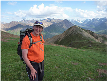 Woman wearing ballcap and daypack smiles while standing on green mountainscape