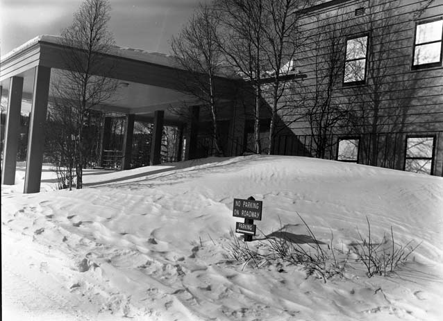 black and white image of a hotel covered in snow