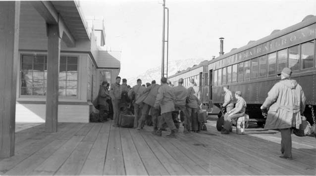 black and white image of soldiers at a train depot
