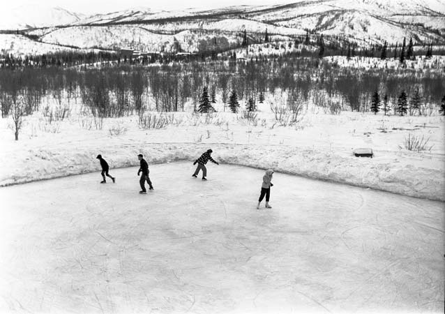 black and white image of four people skating on an ice rink