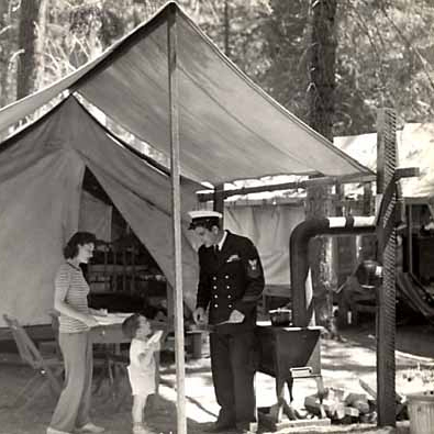 A sailor in uniform with woman and child in tent