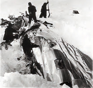 snow covered wreckage of silver plane with men around it