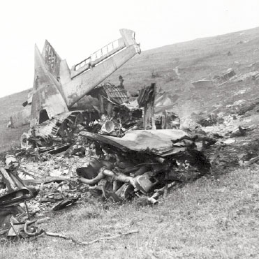 Black and white photo of airplane debris on hill