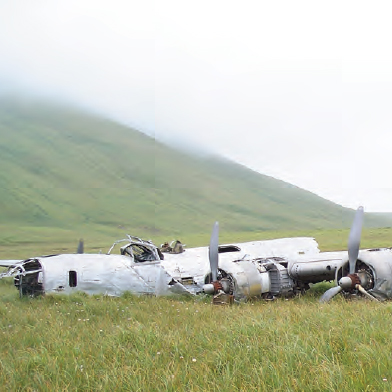 Color photo of plane wreckage in grass, hill beyond