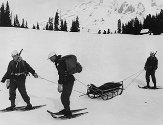 B&W; soldiers on snowshoes tow sled with person in it