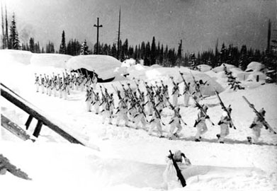 B&W photo of soldiers in white with skis over their shoulder