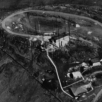 B&W photo of dirt road circling radio towers and small white building