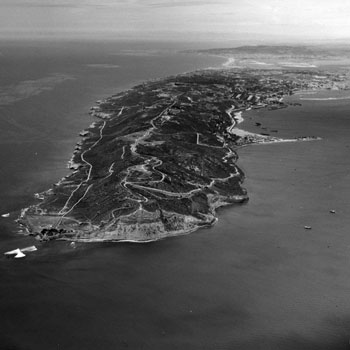 B&W aerial view showing peninsula sticking out into a bay and ocean