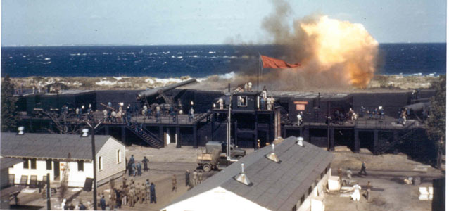 color photo of large explosion atop fort walls, ocean beyond