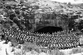 B&W large group of soldiers post in front of cave entrance