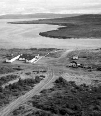 small buildings and dirt roads shown from the air, B&W