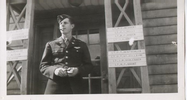 A man in uniform stands on a porch with many name signs