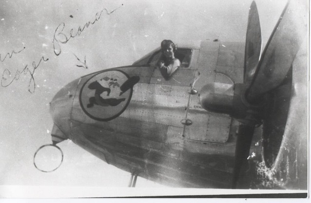 A man hangs out of the cockpit of a prop plane with a beaver insignia on the nose