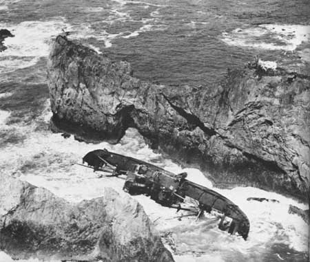B&W photo of ship on its side amongst rocks and crashing waves