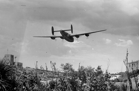 B&W photo of plane flying low over landscape