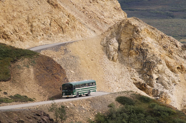 A bus winds around a dirt mountain road